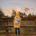 A little girl with a moose backpack in her yellow rain poncho